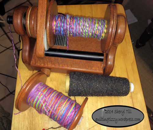 Yarn I spun from Loraine's roving left front.  Black silk yarn for plying on front right.  Plied yarn on the Hansen Mini Spinner.